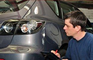 Car repairman examining car damage