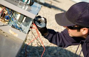 A repairman fixing an hvac unit