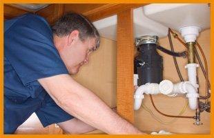 Man repairing underneath sink.