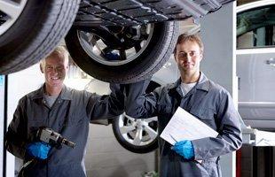Mechanics inspecting a car's tires