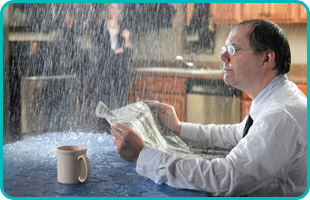A man is reading a newspaper while waters from leaked pipes pouring on him