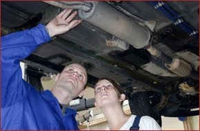Mechanic and car owner looking at the car's muffler