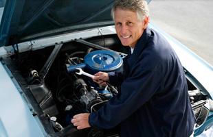 Mechanic repairing classic car engine