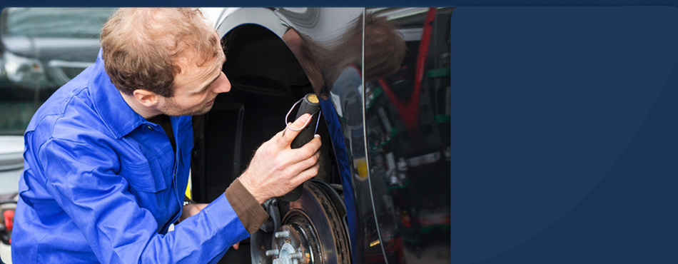 Mechanic inspecting car brakes