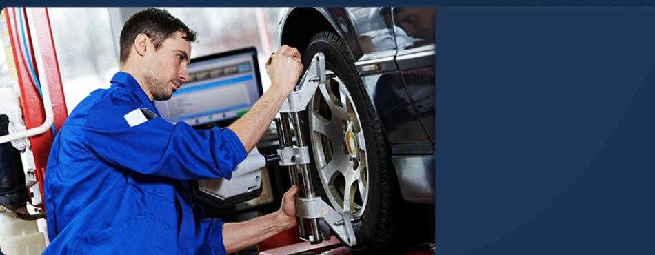 Mechanic inspecting tire alignment
