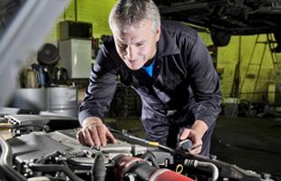 Mechanic inspecting car engine