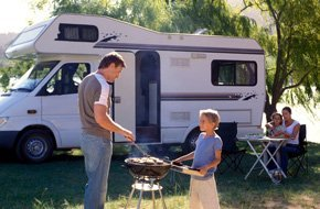 a father and son grilling with a background of a RV