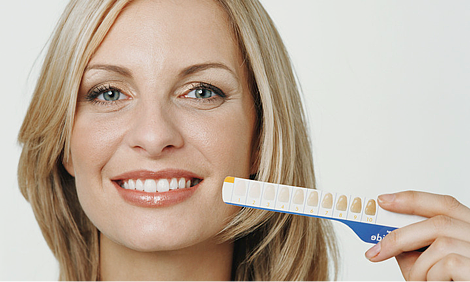 Woman holding a teeth whitening chart