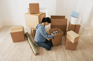Young woman looking at contents of moving boxes in new home