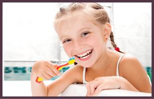 Happy kid brushing her teeth