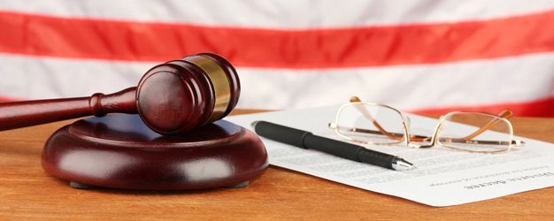 gavel, pen, eyeglasses and documents with USA flag in background