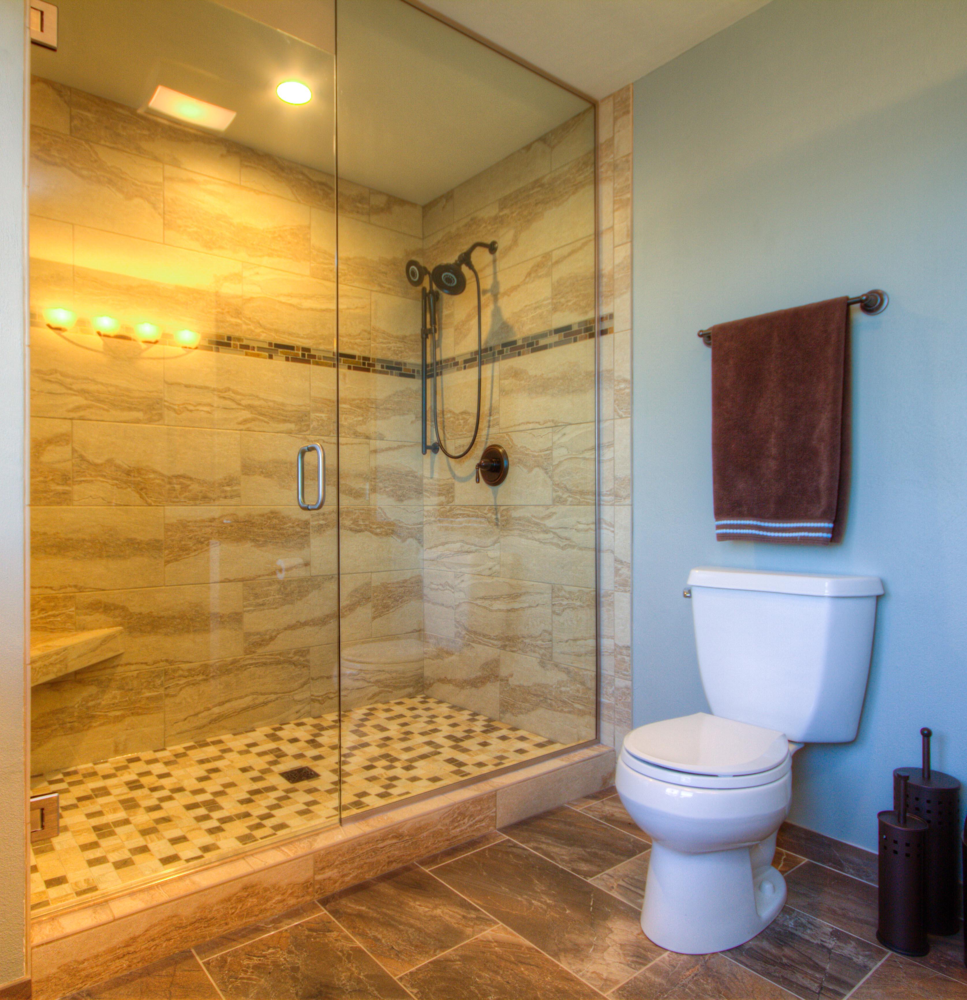 Bathroom Design, custom shower with a curb, frameless glass shower surround, dark brown bathroom floor, light beige shower tile