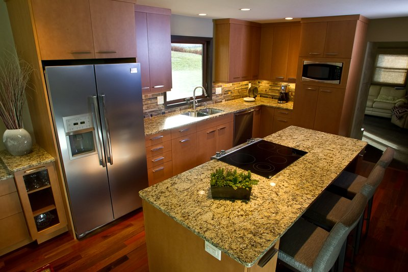 Kitchen Remodeling and Design, l-shape kitchen design, medium brown kitchen cabinets, slab door style, frank lloyd wright inspired backsplash, granite countertop, stove in the island