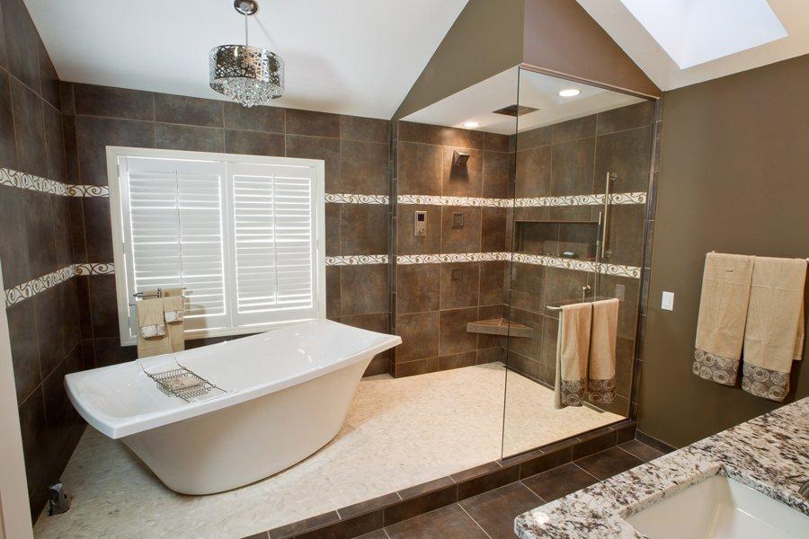 Bathroom Design, luxurious bathroom design, master bathroom design, white kohler tub, freestanding kohler tub, tub and shower separated, cream pebble bathroom floor tile, chandelier above the tub, white wooden shutters in the bathroom
