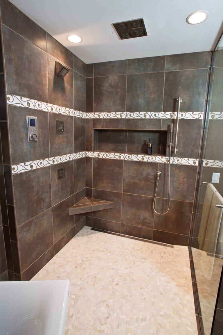 Bathroom Design, large custom shower, dark brown shower tile, shampoo niche, shower body sprays, corner shower bench, linear shower drain, white pebble bathroom floor