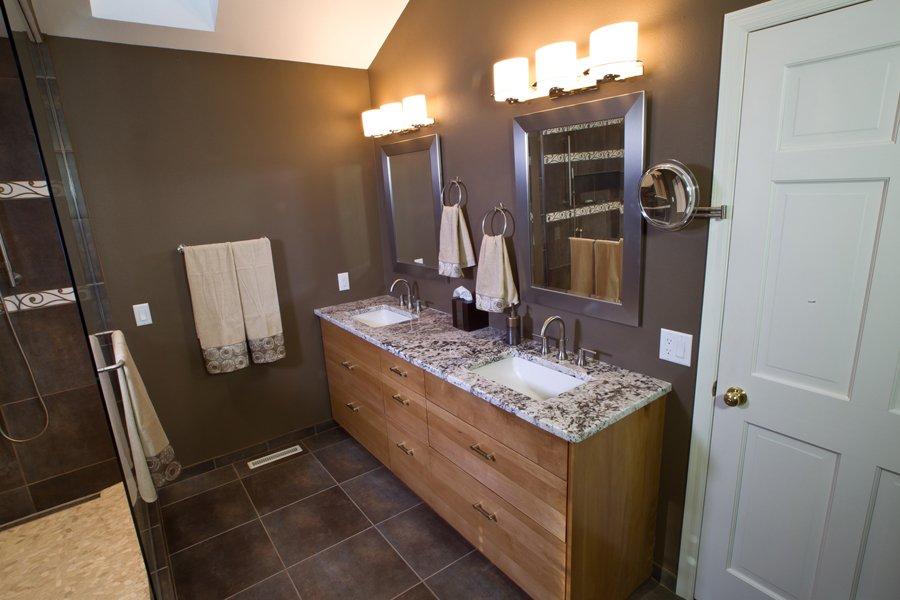 Bathroom Design, double sink vanity, three light vanity light, brushed nickel mirror frame, dark brown bathroom tile, dark brown bathroom walls, dark brown paint color