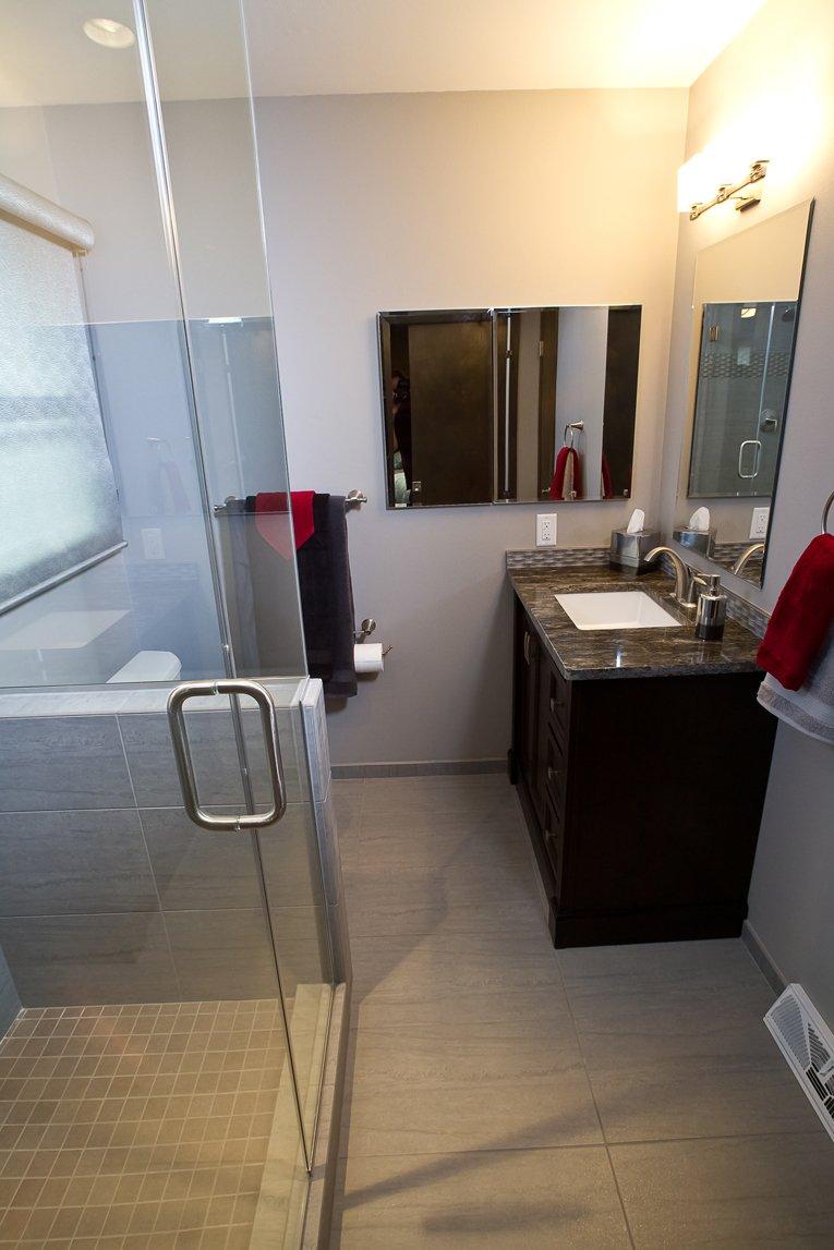 Bathroom Design, small bathroom design, small shower design, small vanity design, half wall  in the shower, light blue shower tile, aqua shower tile, glass shower door, dark brown vanity cabinet, dark grey granite countertop