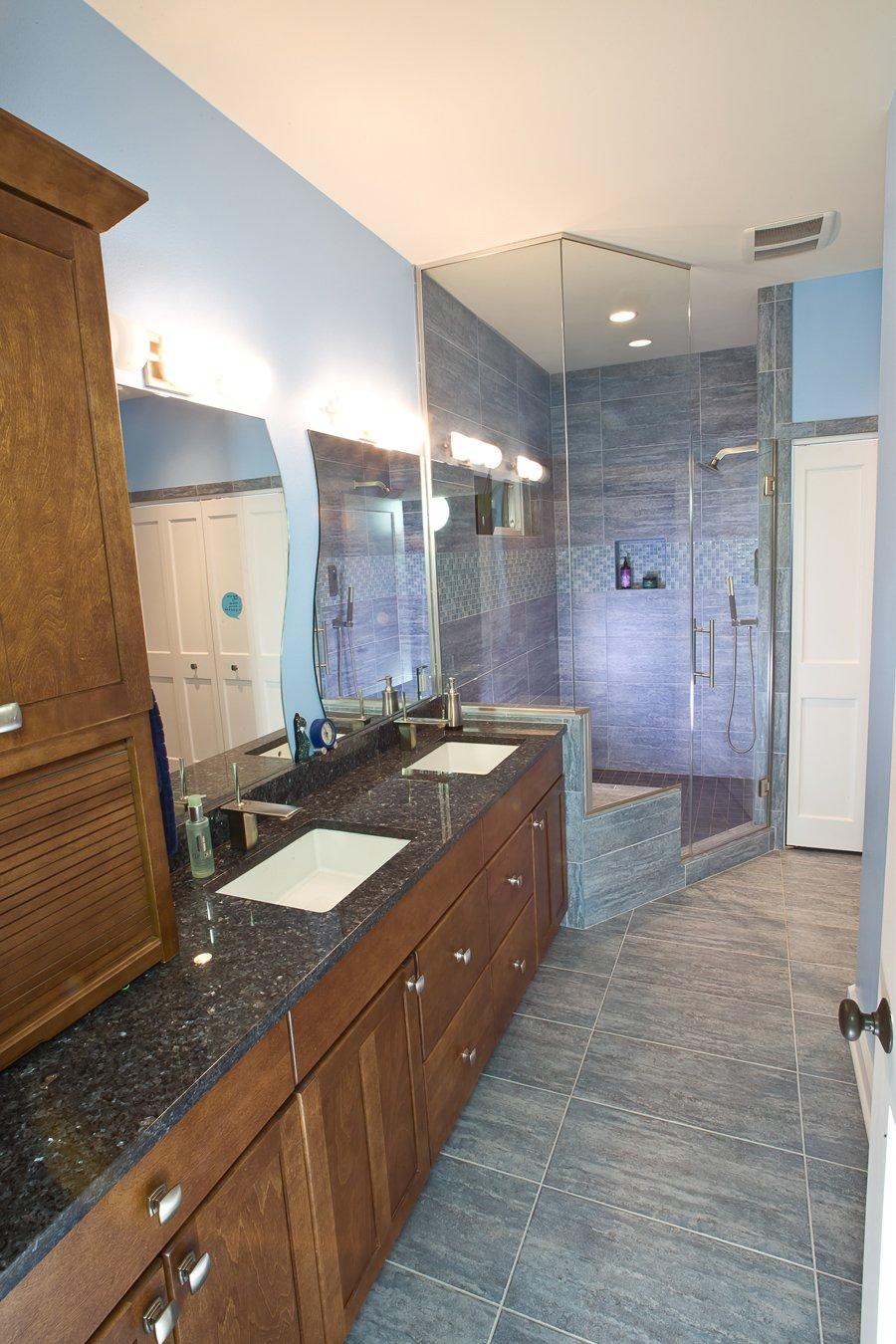 Bathroom Design, blue bathroom tile, corner shower, large corner shower, frameless shower glass surround, double sink vanity, storage vanity tower, dark granite countertop