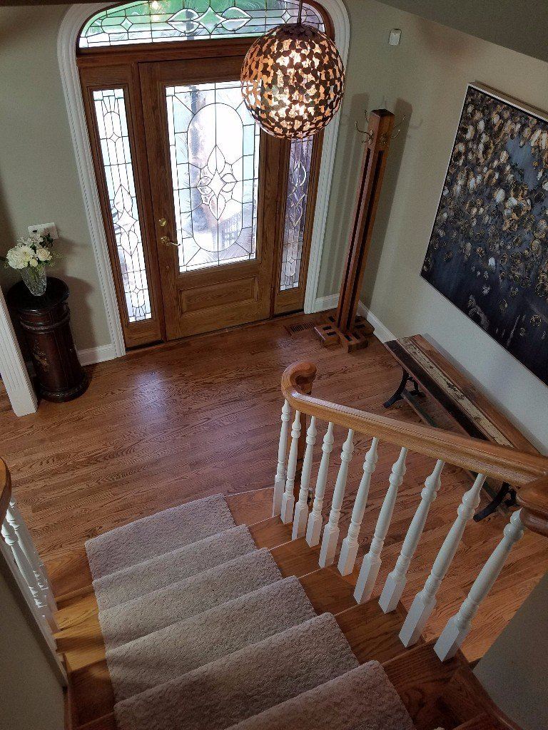 transitional entryway, carpet on the stairs, white spindles, stained railing, oak staircase, oak wood flooring, entryway globe chandelier,