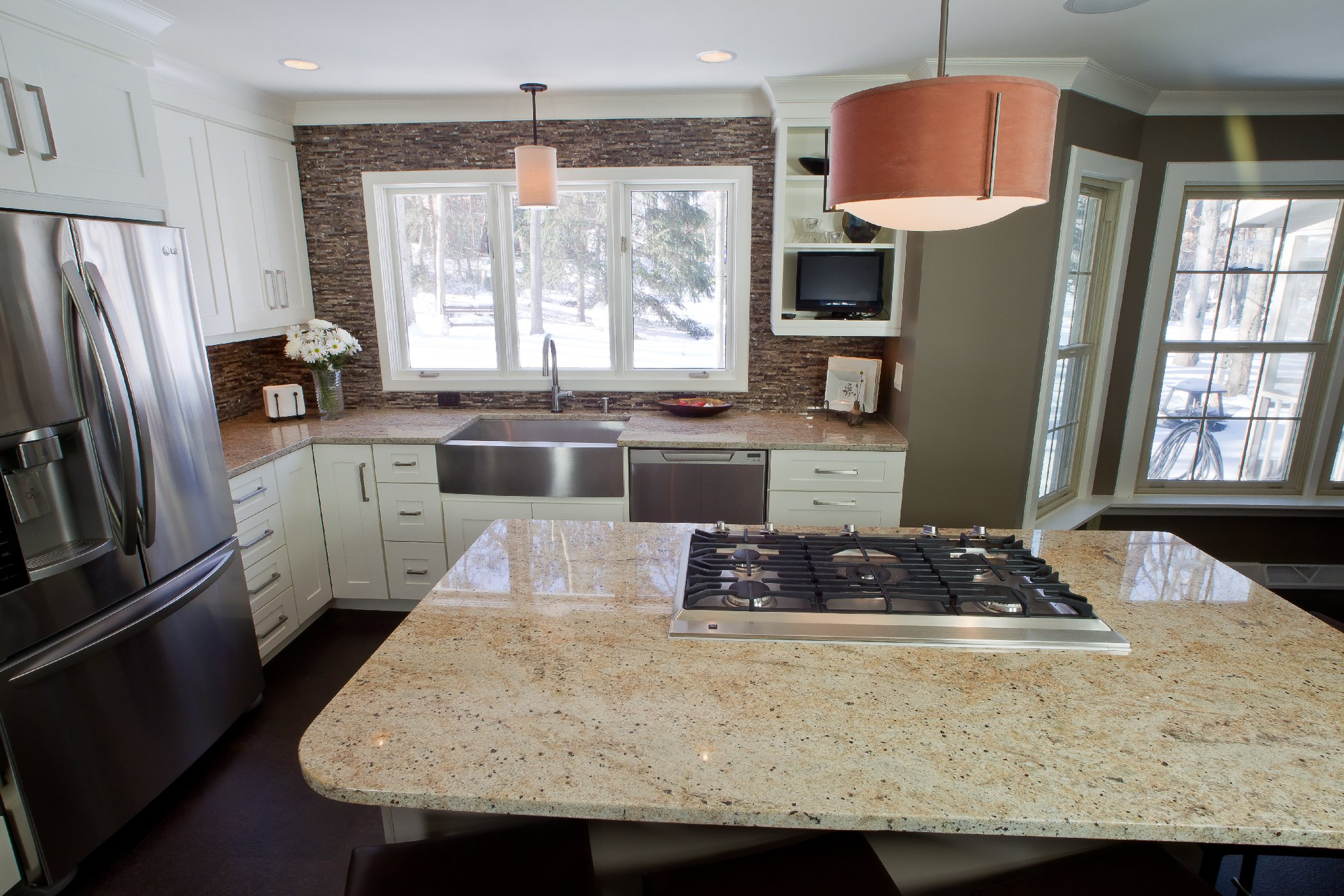 Kitchen Remodeling and Design, cooktop in the island, large sink window, dark brown backsplash, tv kitchen shelf,