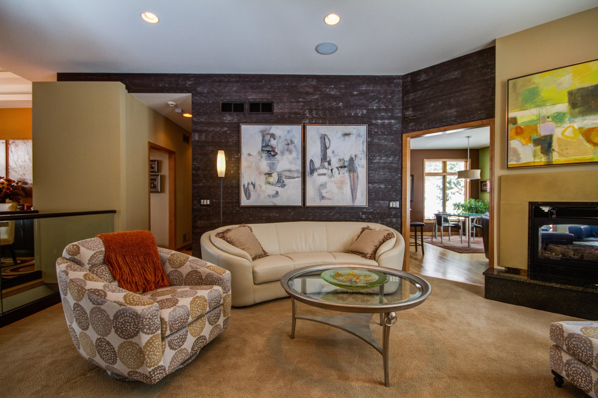 chocolate brown accent living room wall, abstract artwork above the sofa, curved leather sofa, round glass chaddock coffee table