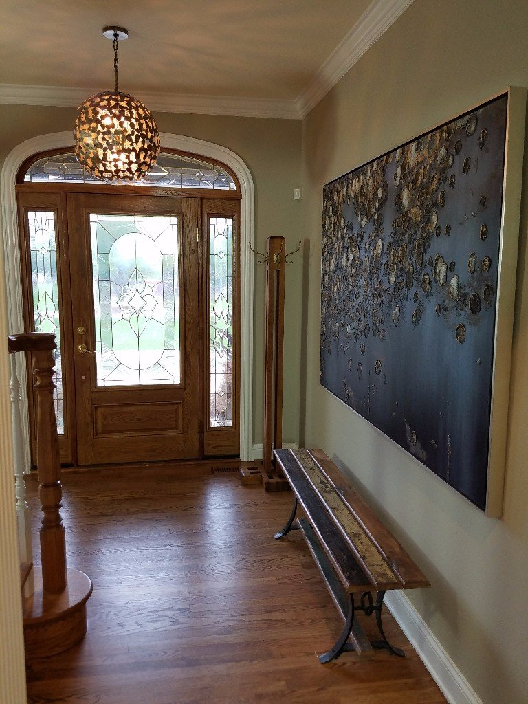 transitional entryway, meteor shower picture, left bank meteor shower, entryway bench, globe entryway chandelier, arched entryway door, white trim, white crown molding entryway