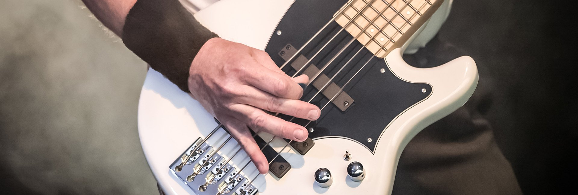 close up of wristbanded musician picking white bass guitar