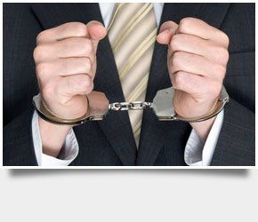 A man in a corporate suit handcuffed