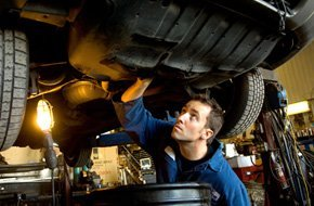 Auto repairman inspecting car