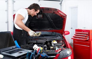 A worker working the engine of the car