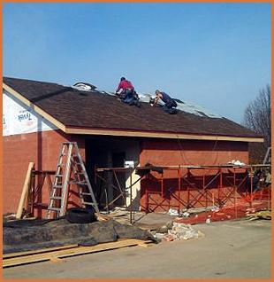 Two man installing metal shingles