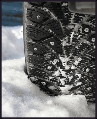 A snow covered road and a car tire