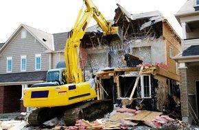 Backhoe demolishing a house