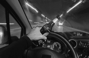 Driver holding beer bottle while driving