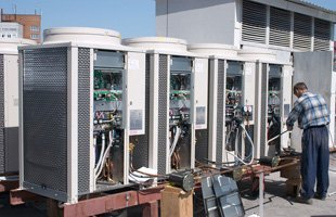 Contractor maintaining commercial air conditioner