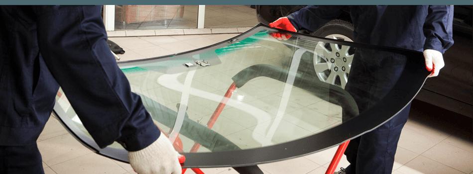 Mechanics holding a windshield