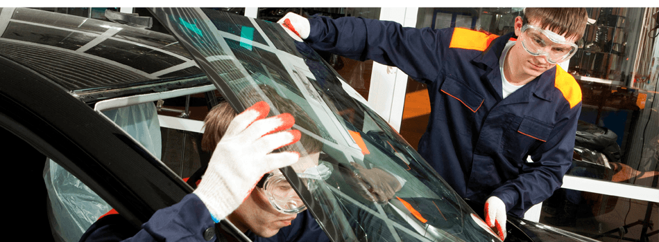 Mechanics replacing the windshield of a black car