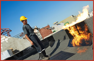 A man installing flat roof in a commercial building