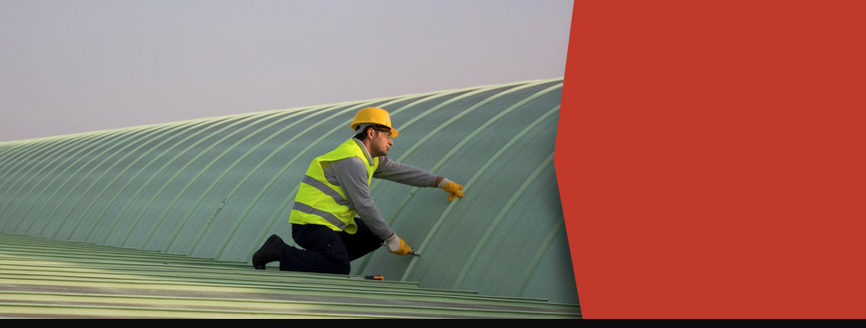 A staff maintaining the roof of a commercial building