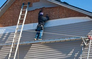 Man repairing roof siding