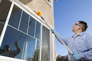 Guy with a Webster tool removing cobwebs and spider