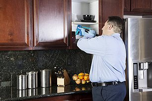 Guy putting bait in cabinets