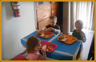 Three liitle kids eating