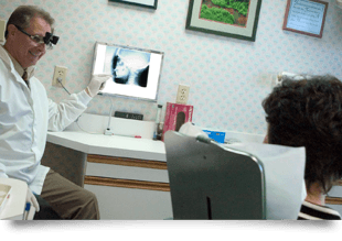 A dentist is checking his patient while showing an x-ray of a teeth