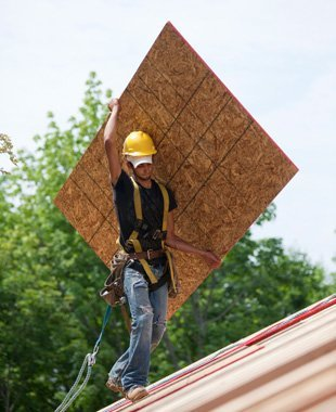 construction worker installs roof