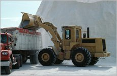 A yellow bulldozer pouring gravel to a truck