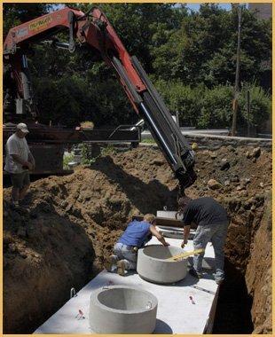 Three men installing septic tank