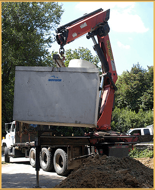 Excavator lifting the septic tank
