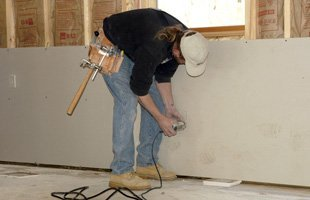 Man using a drywall router to cut out hole for electric outlet