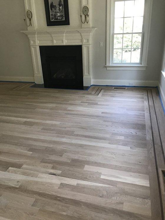 Hardwood floor with trim around fireplace - before